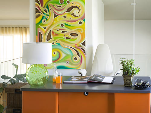 whimsical fun in this modern styled home office.a reclaimed metal desk from the 50's was repainted in this vibrant orange.other vibrant colors of lime in the glass desk lamp and multi colors in the original artwork give a sense of energy to the room.